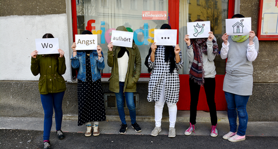 Jugendliche mit Zetteln vor dem Gesicht