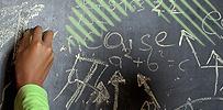 Hand schreibt auf Tafel