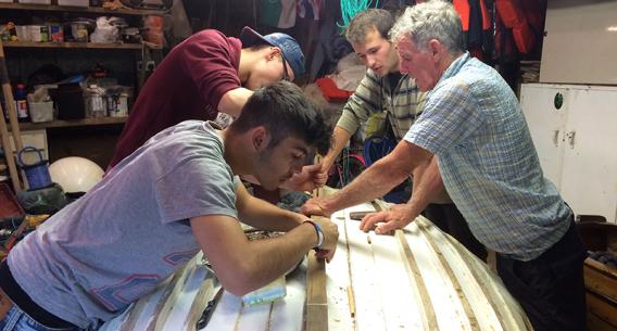Jugendliche beim Boot reparieren