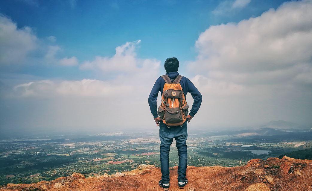 Jugendlicher mit Rucksack von hinten der auf einem Felsen steht und ins Land schaut