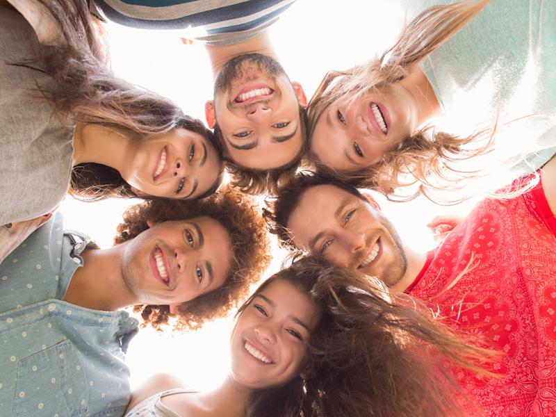6 Jugendliche schauen von oben in die Kamera, sie stehen im Kreis