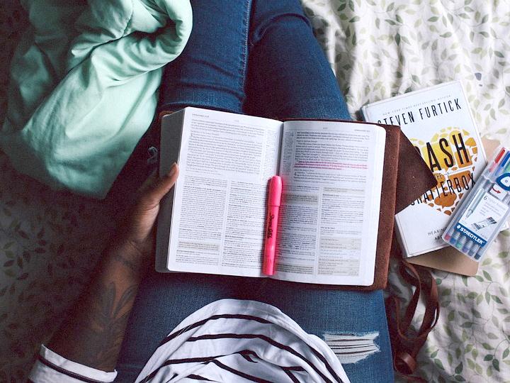 Mädchen sitzt auf Couch und hat ein Buch auf dem Schoß