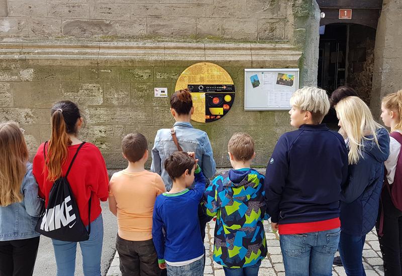 Kinder stehen mit dem Rücken zum Bild und schauen auf Kirche