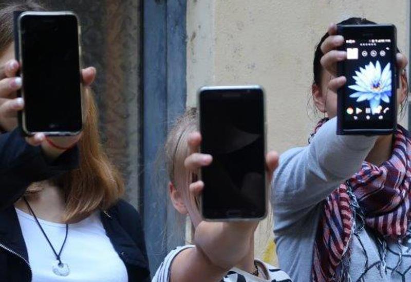 3 Mädchen halten Handys in die Kamera und vor ihr Gesicht
