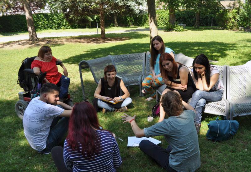 Jugendliche sitzen auf einer Wiese im Park