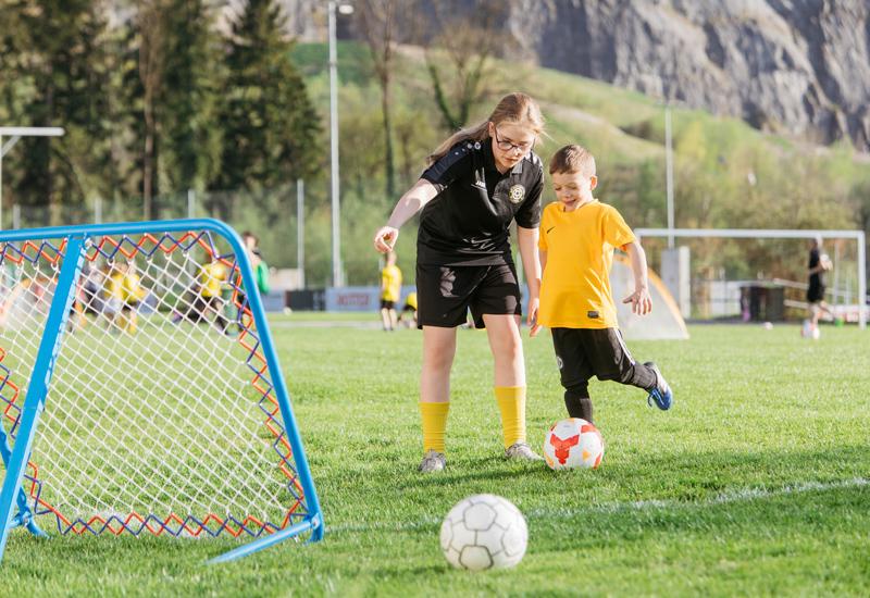 Mädchen und Junge beim Fußballspielen