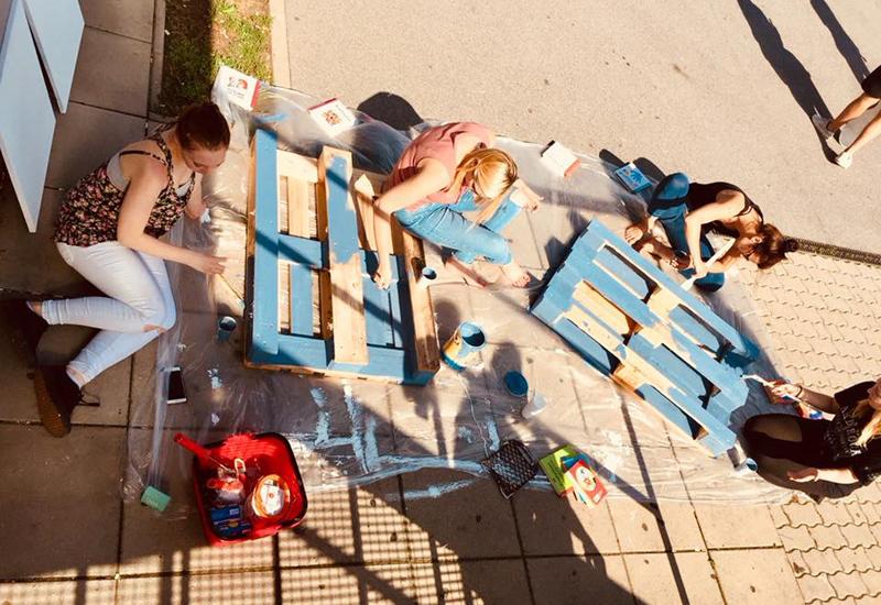 Mädchen auf selbstgebauten Palettenmöbeln von oben fotografiert