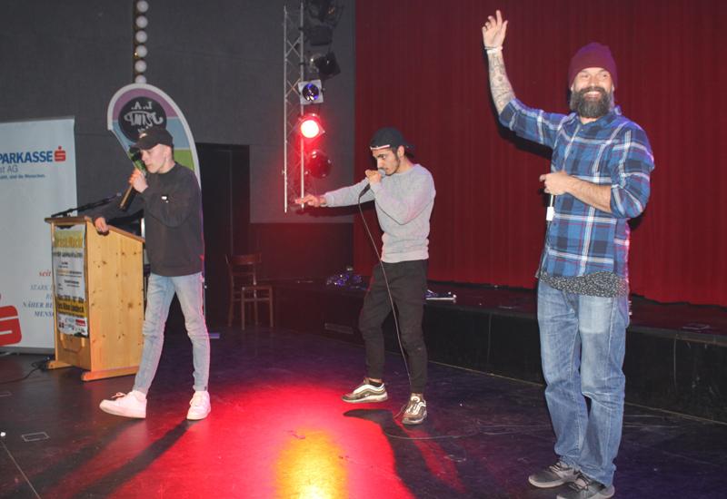 3 Jugendliche auf der Bühne mit Mikros