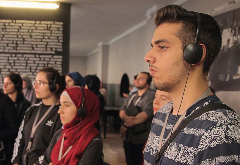 Jugendliche stehen mit betroffenen Gesichtern und Kopfhörern auf vor Museumstafeln