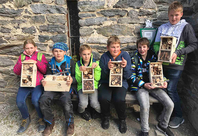 Kinder mit Insektenhotels in der Hand