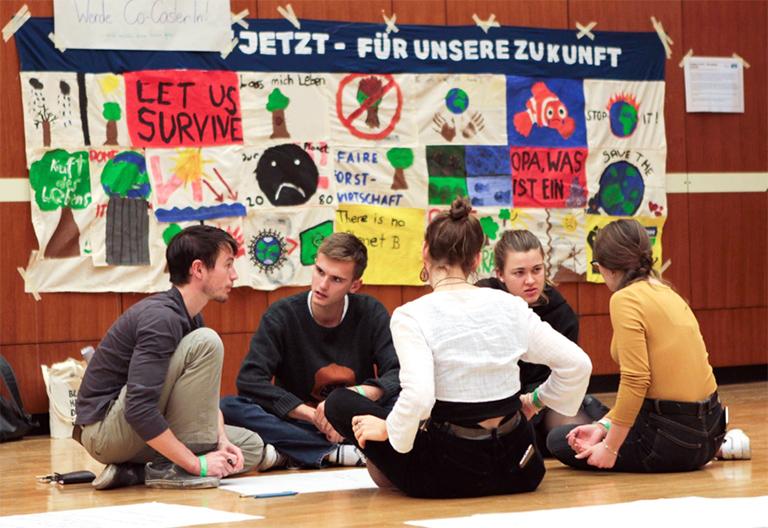 Jugendliche sitzen am Boden und diskutieren, dahinter selbst gemaltes Plakat