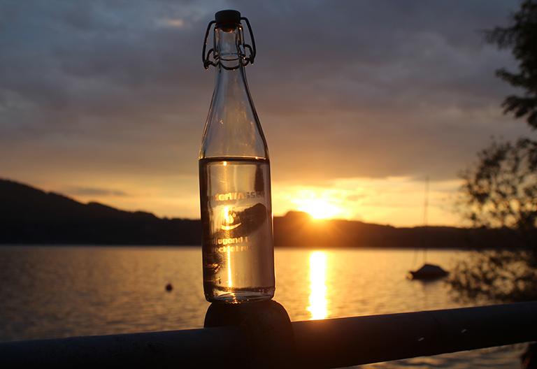 Glasflasche mit Wasser im Vordergrund, dahinter Sonnenuntergang und See