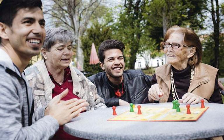 Jugendlicher mit alten Menschen beim Brettspielen