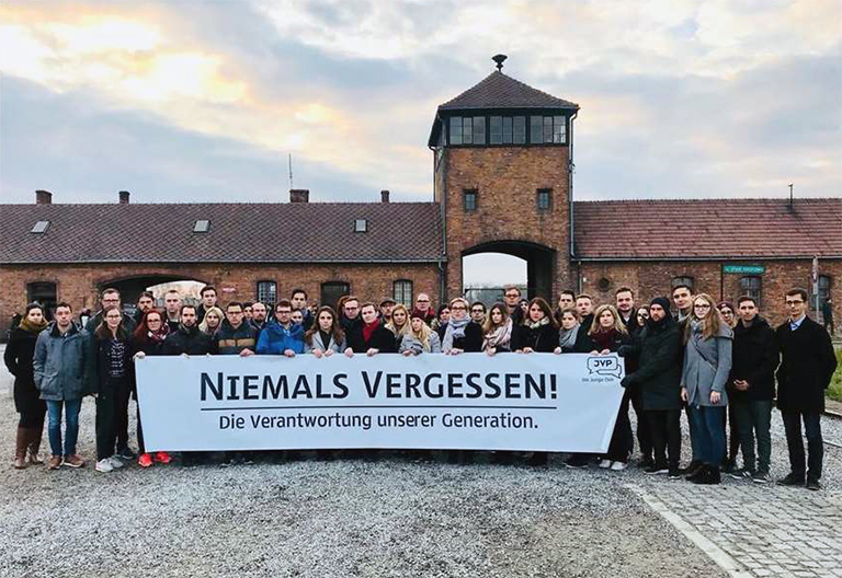 Gruppe von Jugendlichen steht mit Transparent vor KZ